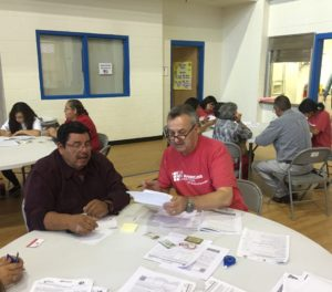 Amir helps a client complete his citizenship application at a New Americans Campaign workshop